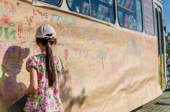 画在墙壁上的逗人喜爱的小女孩背面图一张图片 免版税图库摄影