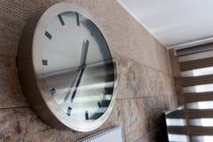 在墙壁上的金属手表 库存照片