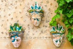 在墙壁上的面具有印刷品的绿色植物的 库存图片