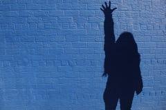 在墙壁上的阴影妇女 库存照片