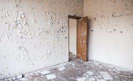 在墙壁上的破裂的油漆和打开木门 免版税图库摄影