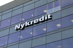 在墙壁上的Nykredit标志在玻璃buildin 免版税图库摄影