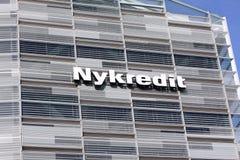 在墙壁上的Nykredit标志在玻璃buildin 图库摄影