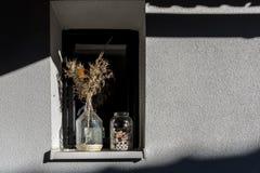 在墙壁和一个适当位置上的阴影与有石头和干花的一个玻璃容器 免版税图库摄影