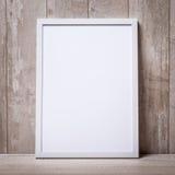 在墙壁和地板上的空白的白色画框 库存图片