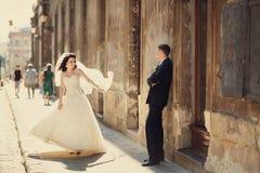 在墙壁户外利沃夫州附近修饰摆在与他美丽的新娘 免版税库存照片