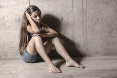 在墙壁旁边的哀伤和孤独的女孩 免版税库存图片