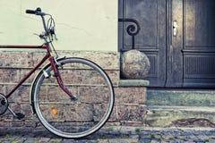 在墙壁时髦的自行车附近停放的轮子 库存照片