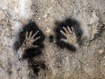 在墙壁现代艺术的手在洞 库存照片