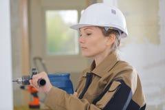 在墙壁的女性建造者钻孔 库存照片