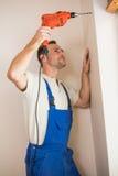 在墙壁的建筑工人钻孔 免版税库存照片