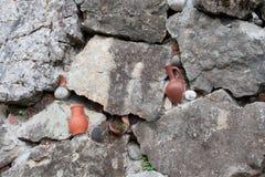 在墙壁的残破的土制瓶子 库存照片
