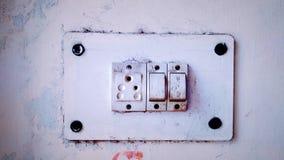在墙壁的白色老土气电子插口 库存图片