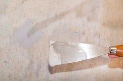 在墙壁的被修补的孔有在修平刀的膏药的 图库摄影