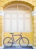 在墙壁窗架行家生活方式的葡萄酒自行车 库存照片