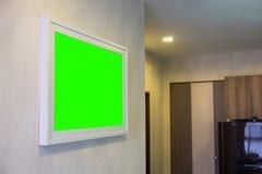 在墙壁绿色屏幕上的装饰照片框架倒空框架 免版税图库摄影