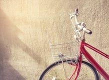 在墙壁背景葡萄酒样式作用的红色自行车 库存图片