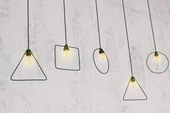 在墙壁附近的垂悬的电灯泡 原始的电灯泡 库存照片