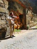 在墙壁附近的小提琴手 免版税库存图片