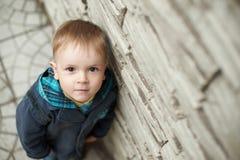 在墙壁附近的小男孩 库存照片