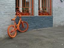 在墙壁附近的橙色自行车 免版税库存图片