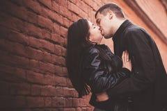 在墙壁附近的爱恋的夫妇 免版税库存图片