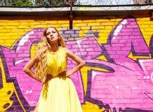 在墙壁附近的白肤金发的女孩有街道画的。街道时尚 库存照片