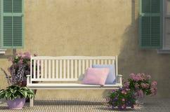 在墙壁附近的白色长凳 库存图片