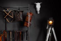 在墙壁附近的皮革提包和皮带 免版税库存照片