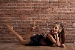 在墙壁附近的砖女孩 免版税库存照片