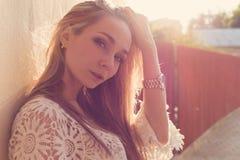在墙壁附近的美丽的性感的嫩女孩,在日落的木篱芭旁边在城市, volntse头发 免版税库存图片