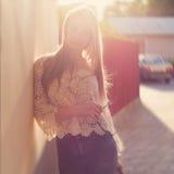 在墙壁附近的美丽的性感的嫩女孩,在日落的木篱芭旁边在城市, volntse头发 库存照片