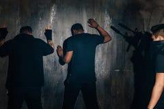 在墙壁附近的被拘捕的匪盗在晚上 免版税库存照片