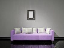 在墙壁附近的紫罗兰色沙发 库存图片