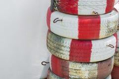 在墙壁附近绘了白色和红色被堆积的轮胎 免版税图库摄影