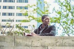 在墙壁顶部的年轻非裔美国人的人阅读书在新的Yo 库存照片