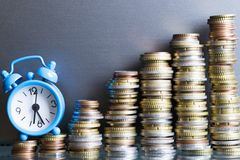 在增长的图从现金硬币,时间的微型闹钟是金钱概念 库存照片