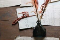 在墨水池的古色古香的翎毛钢笔 免版税库存照片