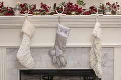在壁炉壁炉台的三只圣诞节长袜 免版税库存照片