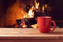 在壁炉的红色杯子在木桌上 冬天和圣诞节假日概念 免版税库存图片