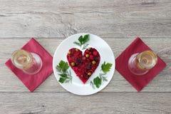 在壁炉边形状做的甜菜根和菜沙拉服务用在板材的草本有两杯的香槟反对木backgro 免版税库存照片