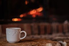 在壁炉边的一个加奶咖啡杯子 库存图片