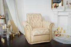在壁炉附近的典雅的椅子 在白色颜色的豪华内部 免版税图库摄影
