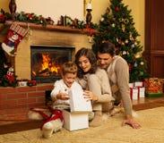 在壁炉附近的家庭在圣诞节房子里 免版税库存照片