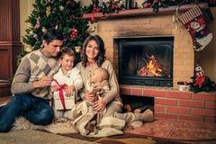在壁炉附近的家庭在圣诞节装饰了房子 免版税库存图片