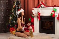 在壁炉附近的美丽的妇女在冬天房子里 免版税库存照片