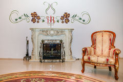 在壁炉附近的葡萄酒扶手椅子 库存图片