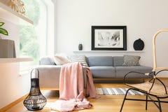 在壁角长沙发投掷的粉红彩笔毯子站立在与简单的海报、灯笼、装饰和大windo的白色客厅内部 免版税库存图片