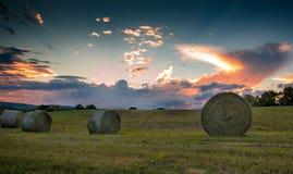在壮观的日落期间,滚动的大包干草在辗压小山被看见 库存图片
