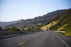 在壮观的高速公路的半经典之作卡车有篱芭和绿色t的 库存照片